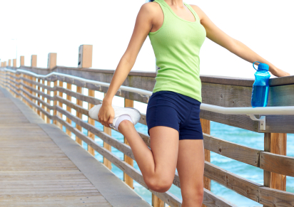 Midsection of healthy young woman stretching her leg during exercise on bridge. Horizontal shot.